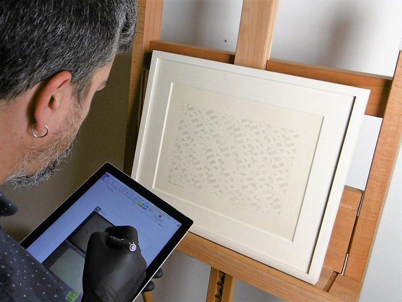 Empleado del museo trabajando con una tablet sobre una obra