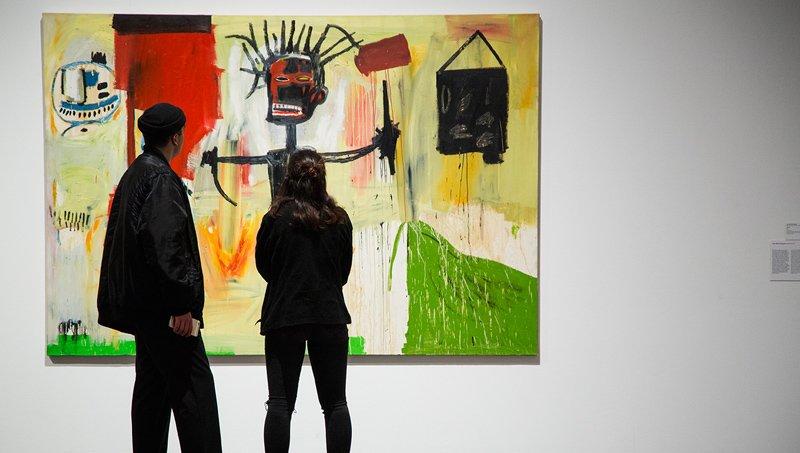 Una pareja de visitantes observan una obra del museo
