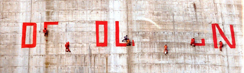 """Activistas en contra de la desaparición del valle de Riaño pintando sobre la presa """"DEMOLICIÓN"""", 1987"""