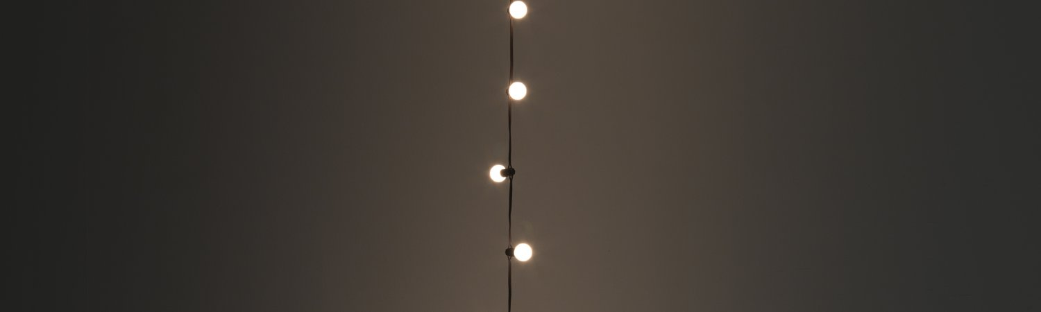 """Felix Gonzalez-Torres """"Untitled"""" (Last Light), 1993. Light bulbs, plastic light sockets, electrical cord, and dimmer switch. Overall dimensions vary with installation. Edition of 24, 6 APs. Published by A.R.T. Press, Los Angeles and Andrea Rosen Gallery, New York. Copyright Felix Gonzalez-Torres. Courtesy The Felix Gonzalez-Torres Foundation. Photographer: Jordi V. Pou. MACBA Collection. MACBA Foundation. Long-term loan of Brondesbury Holdings Ltd."""