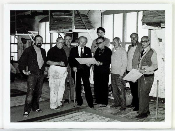 """[Joan Brossa amb els constructors dels decorats per a """"La pregunta perduda o el corral del lleó"""" al taller Germans Salvador, Barcelona, 1985"""