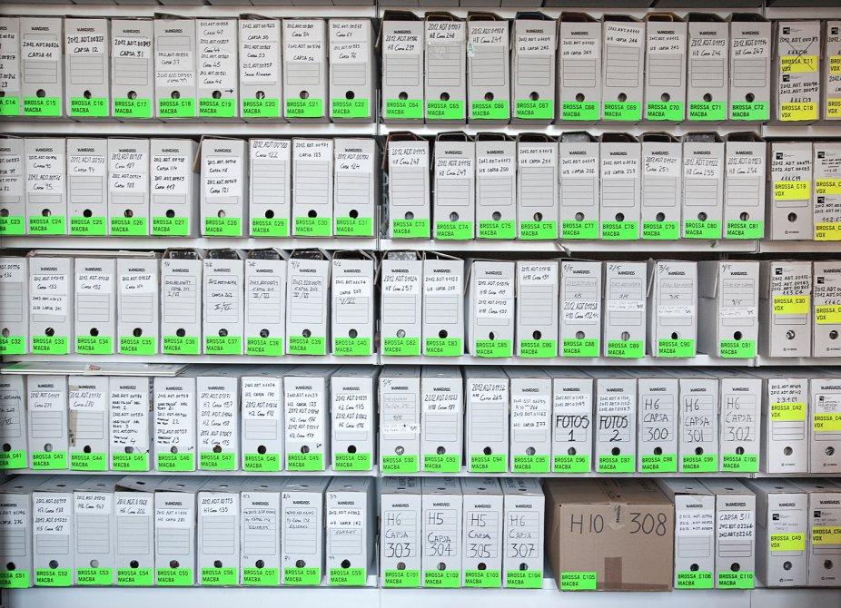 Carpetas colocadas en estanterías con etiquetas verdes o amarillas