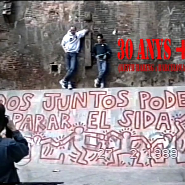 """Captura de vídeo, enregistrament realitzat per César Melero de l'acció del mural """"Tots junts podem parar la sida"""" (1989) de Keith Haring, inclòs en el documental """"30 anys +"""" (2018) de Lulu Martorell y Roger la Puente"""